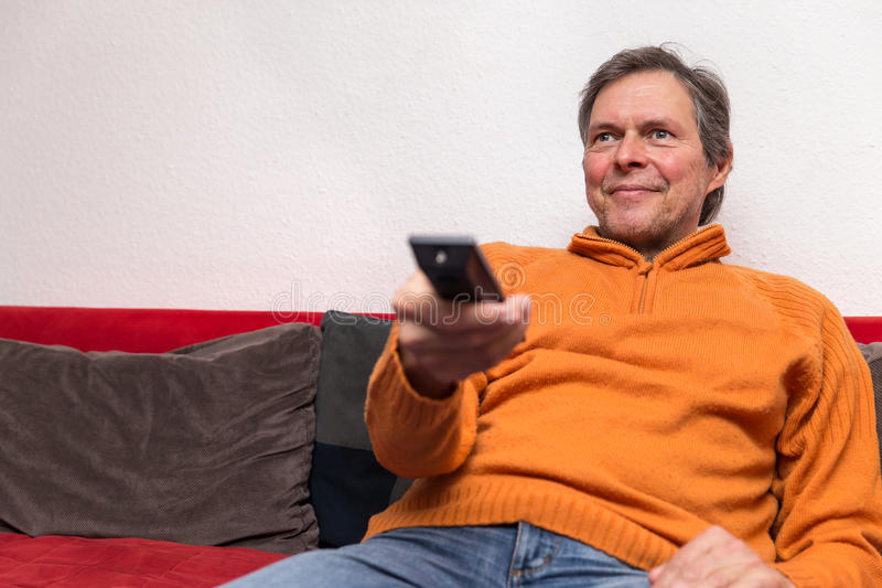 Senior adult with remote control. On a couch stock photo
