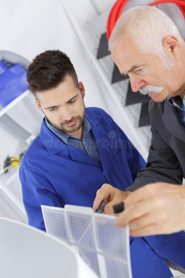 Senior adult repairman device with helper stock photos