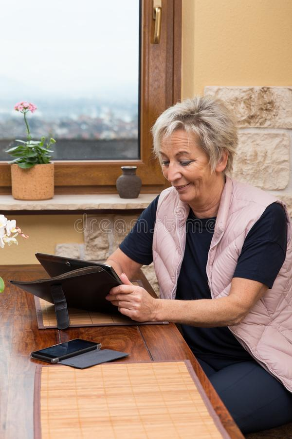Senior adult woman with tablet stock photos