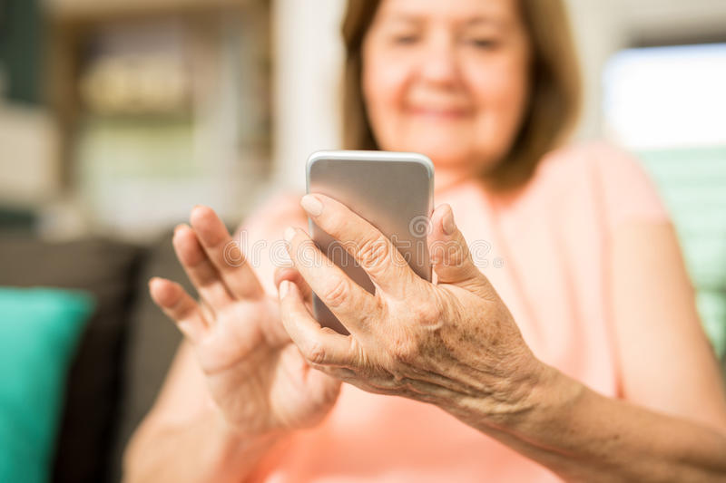 Senior adult woman touching her phone`s screen royalty free stock photography