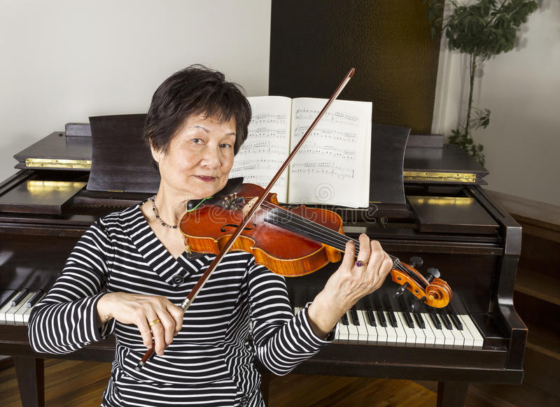 Senior Adult Women Playing the Violin royalty free stock photo
