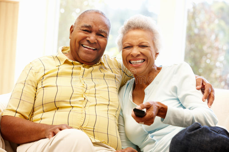 Senior African American couple watching TV stock photography