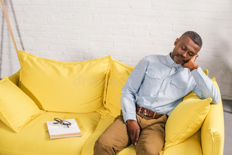 Senior african american man sleeping on couch book and eyeglasses. On sofa stock image