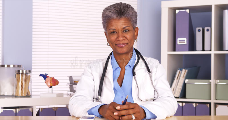 Senior african doctor sitting at desk smiling at camera stock photography