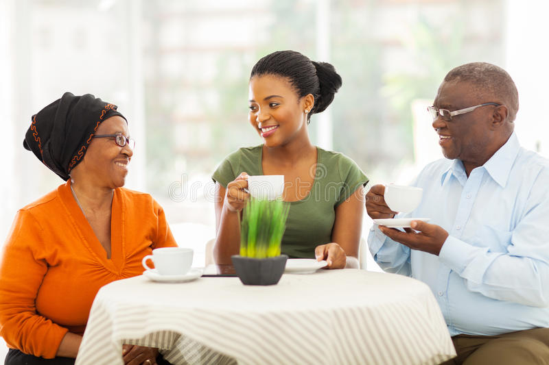 Senior african parents daughter. Loving senior african parents having coffee with daughter indoors stock photography