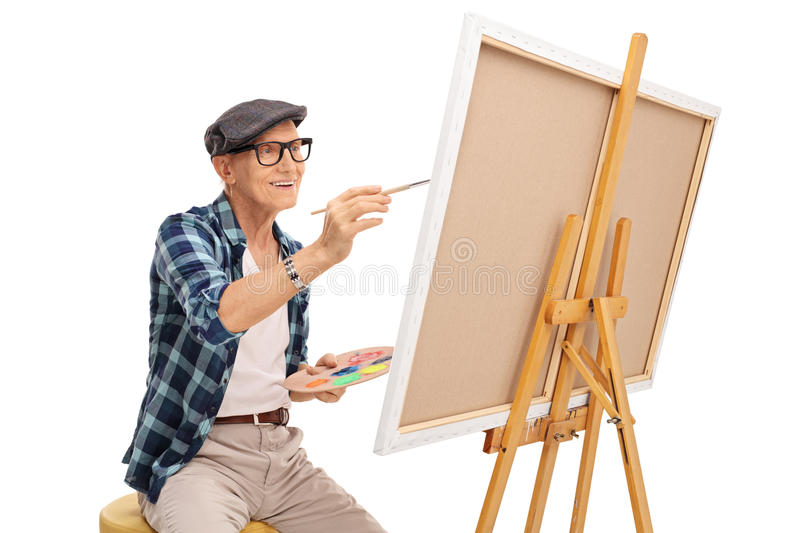 Senior artist painting on a canvas. With a paintbrush isolated on white background stock photo