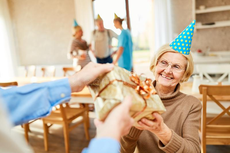 Senior as a birthday girl is happy about gift royalty free stock photos