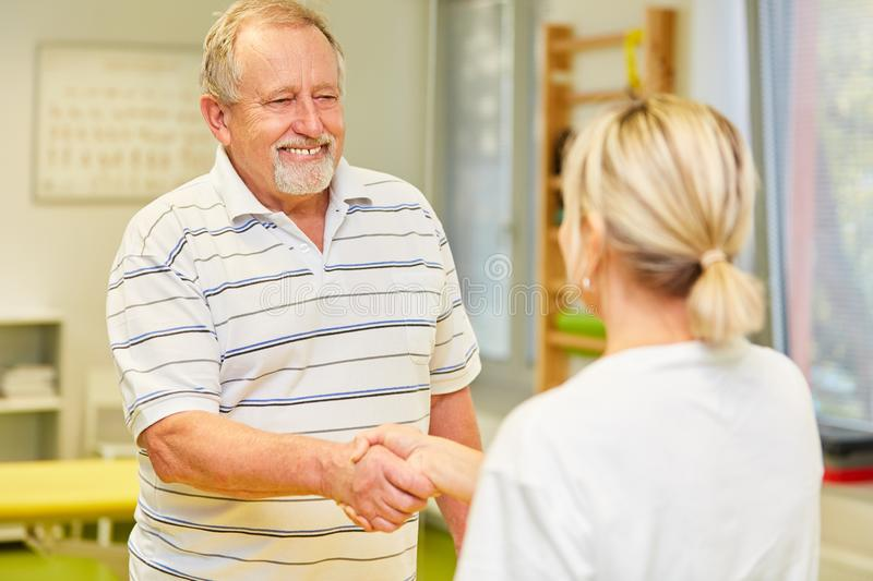 Senior as grateful patient shaking doctor`s hand royalty free stock image