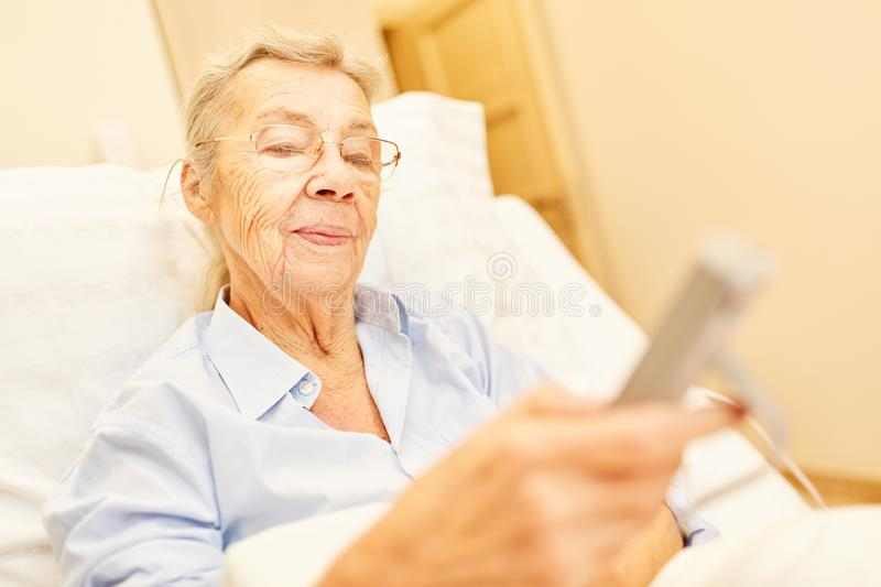 Senior as a patient in the nursing bed stock photos