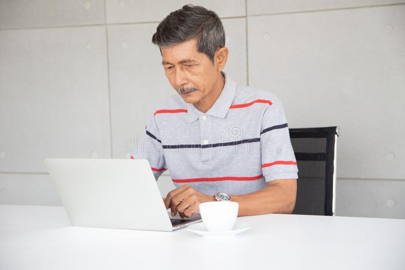Senior Asia businessman in casual  work by use laptop stock image