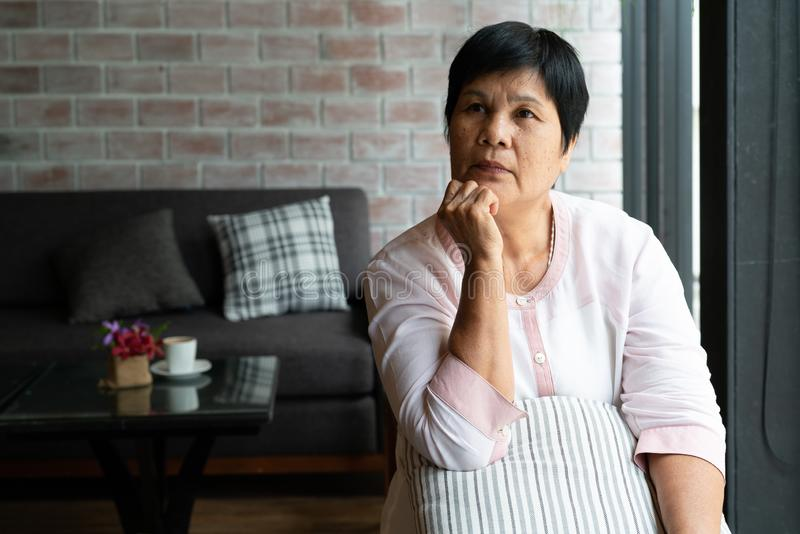 Senior asia woman thinking and looking sideways, thinking and wondering royalty free stock image
