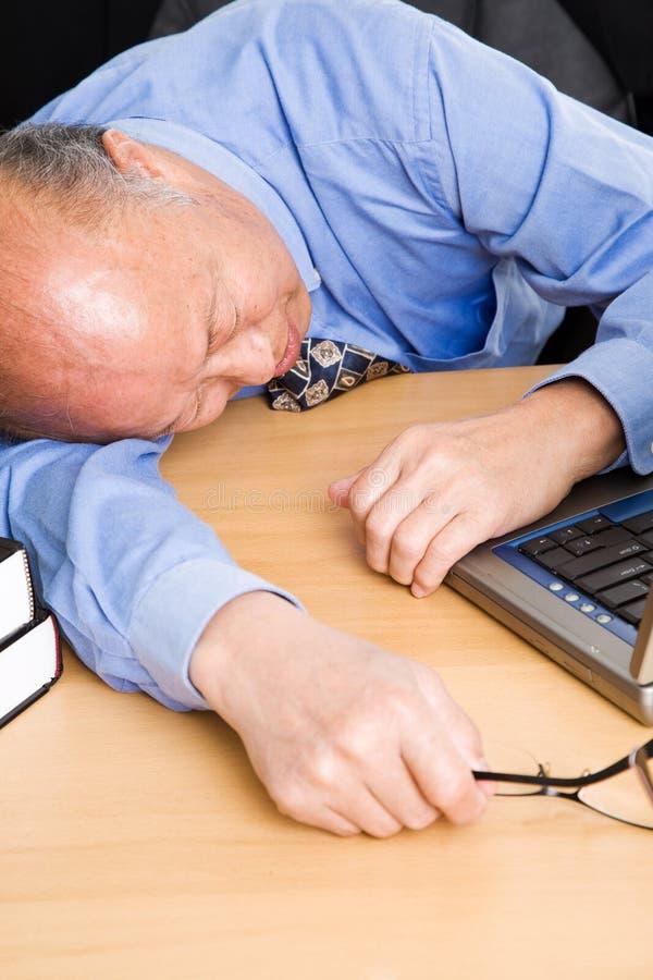 Senior asian businessman sleeping. A senior asian businessman sleeping in the office stock photos