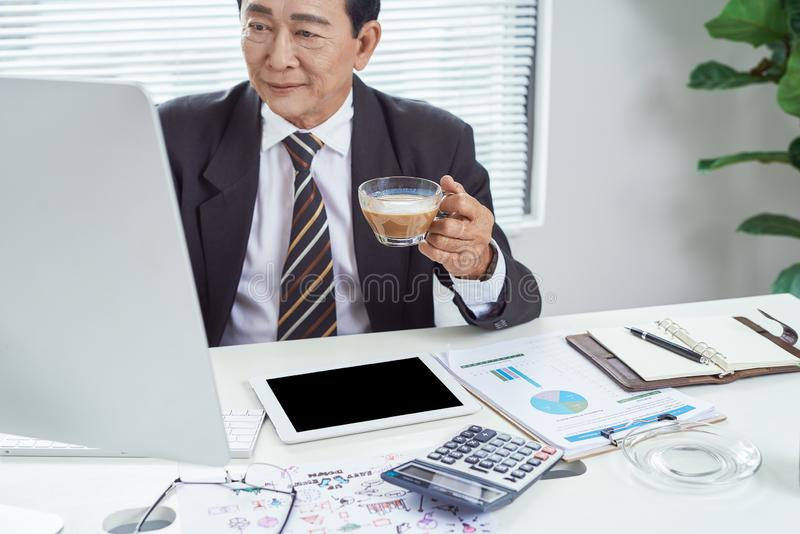Senior asian businessman working at his office desk, business people, office lifestyle concept stock images