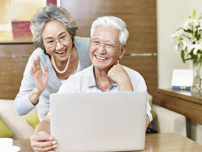 Senior asian couple chatting online stock photo