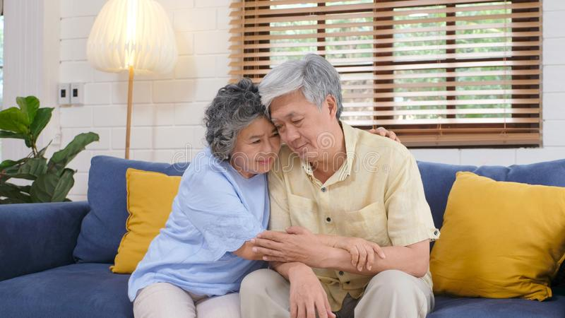 Senior asian couple comforting each other from depressed emotion while sitting on sofa at home living room, old retirement stock photos