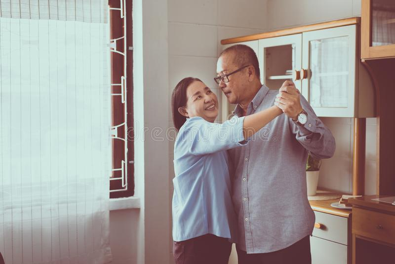 Senior asian couple dancing enjoying at home together,Having fun and love live forever stock photos