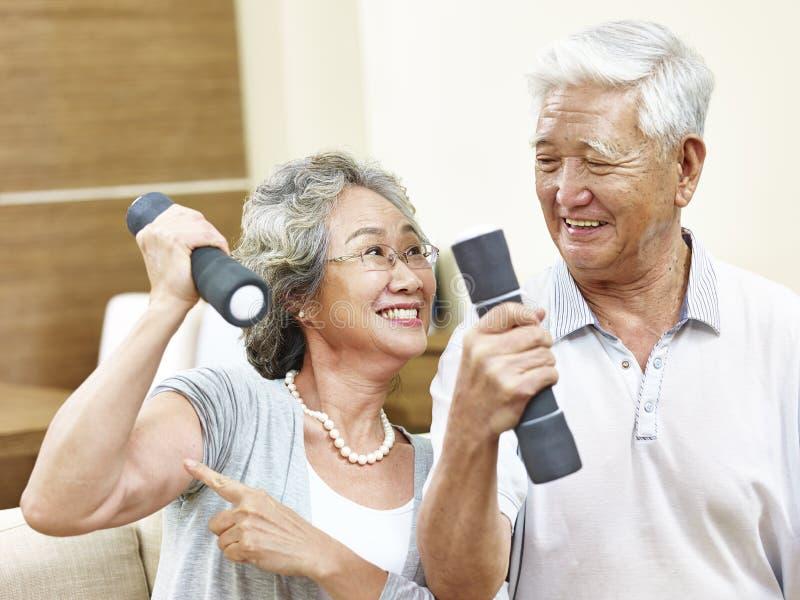 Senior asian couple exercising using dumbbells royalty free stock photo