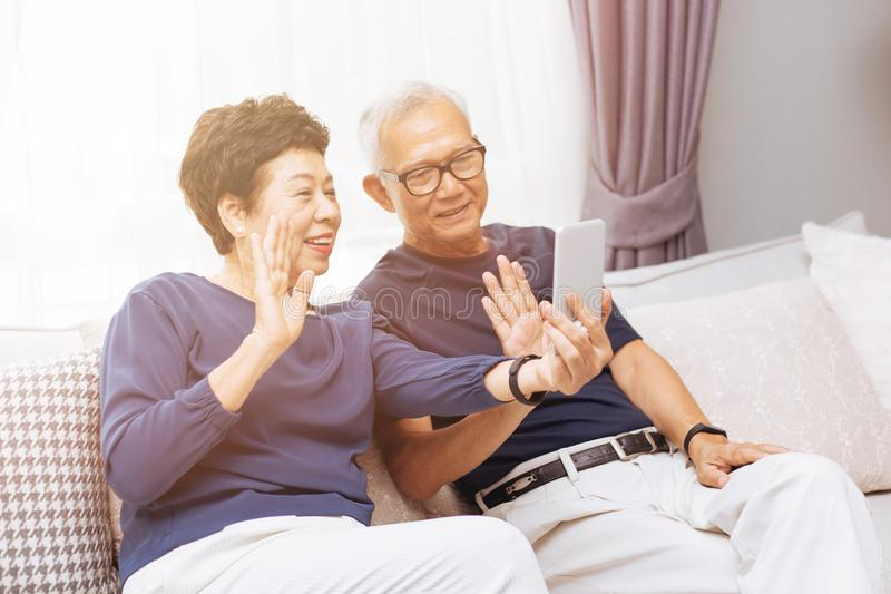 Senior Asian couple grand parents making a video call and waving at the caller. royalty free stock photography
