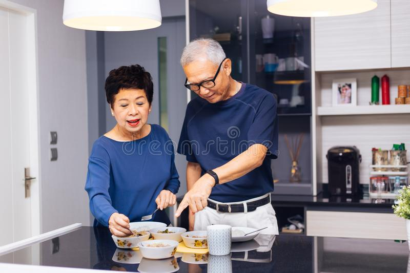 Senior Asian couple grandparents cooking together while woman is feeding food to man at the kitchen. Long lasting relationship stock photo