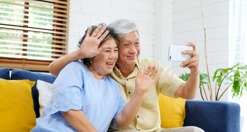 Senior asian couple make video call to family, friend smiling with happiness while sitting at sofa in home living room, old people royalty free stock photography
