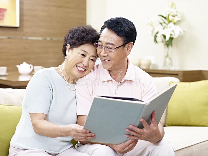 Senior asian couple reading a book together royalty free stock images
