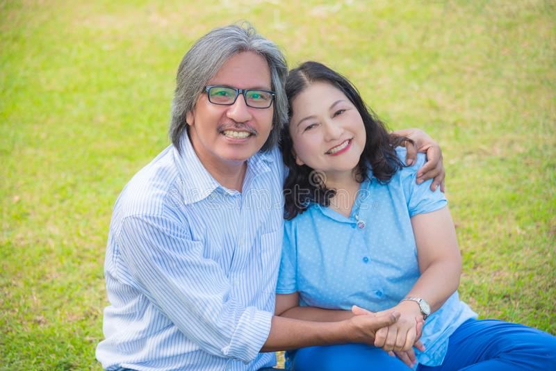 Senior Couple Relaxing In Park Together. Senior Asian Couple Relaxing In Park Together royalty free stock image