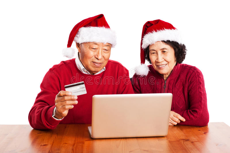 Senior Asian couple shopping online. A shot of senior Asian couple shopping online celebrating Christmas royalty free stock photography