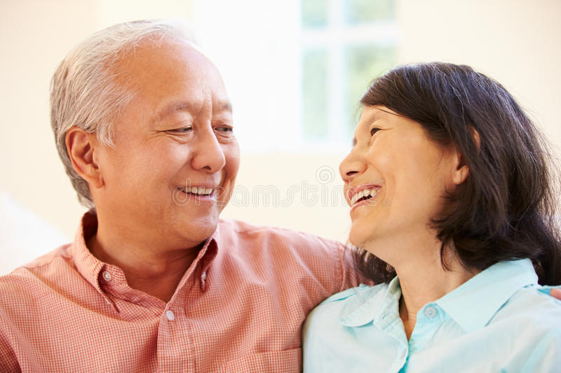 Senior Asian Couple Sitting On Sofa At Home Together stock photo