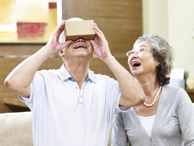 Senior asian couple trying vr device royalty free stock photography
