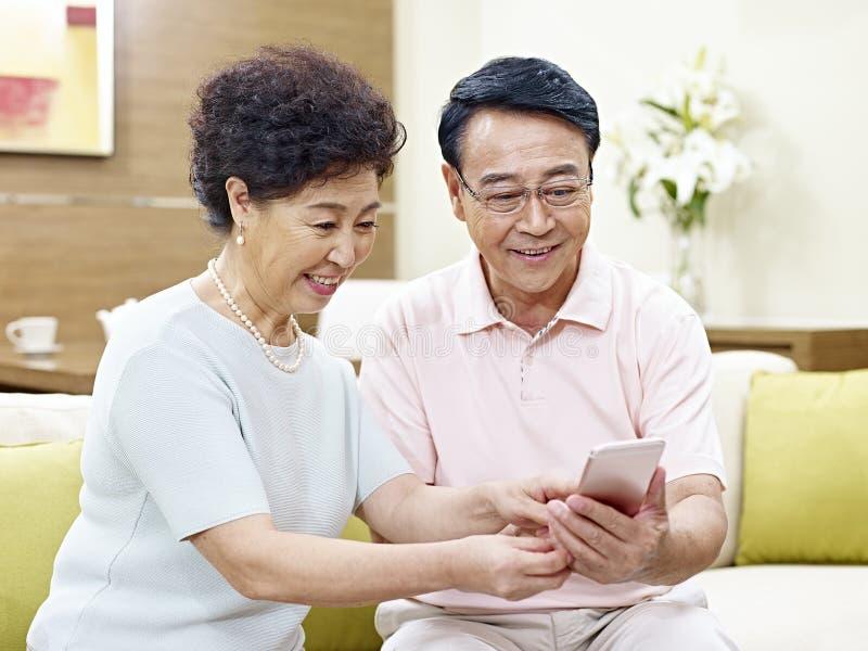 Senior asian couple using mobile phone royalty free stock photo
