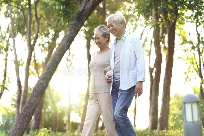 Senior asian couple walking in park stock photo