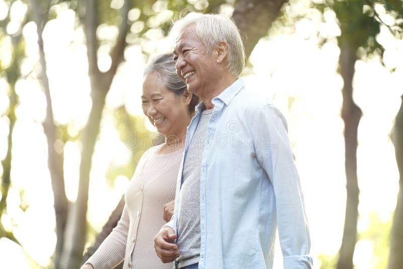 Senior asian couple walking in park stock image