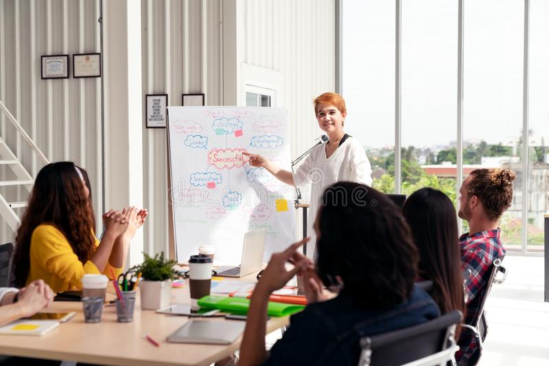 Senior asian creative businesswoman standing and making presentation at modern office happy talking and brainstorming with team stock photography