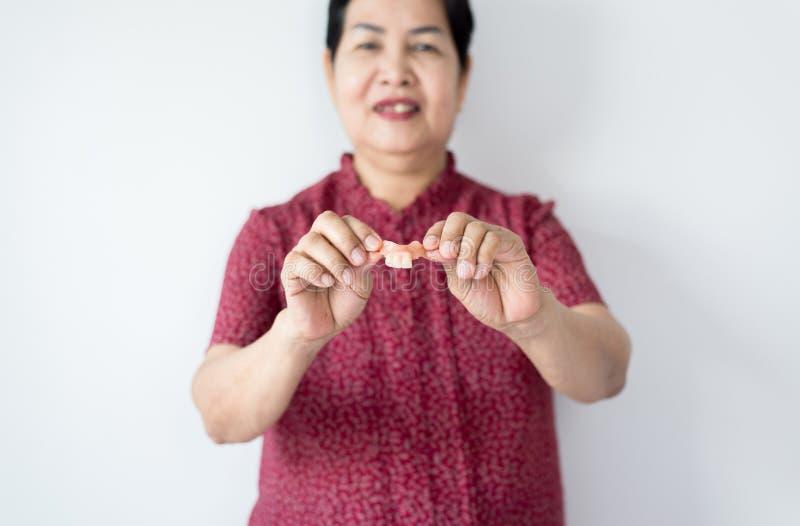 Senior Asian woman is holding dentures in hands,Dental prosthesis,False teeth,Close up. Senior Asian female is holding dentures in hands,Dental prosthesis,False stock photos