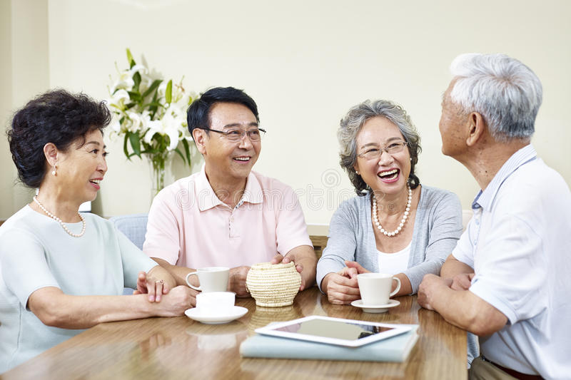 Senior asian friends relaxing chatting at home royalty free stock image