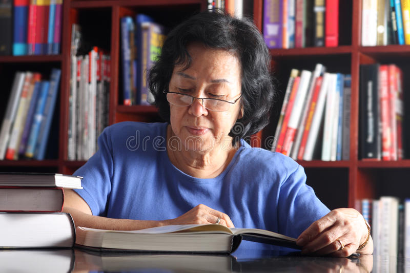 Senior Asian lady reading in library stock images