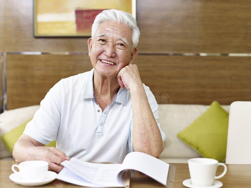Senior asian man reading in study room royalty free stock photo