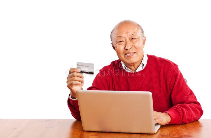Senior Asian man shopping online. A shot of senior Asian man shopping online celebrating Christmas royalty free stock photos