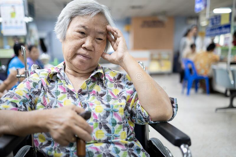 Senior asian patient in wheelchair waiting for a long time,medical examination with the doctor in the hospital,elderly people feel royalty free stock images