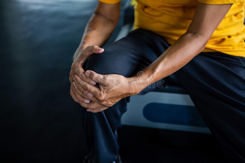 Senior asian sport man injury knee pain  sitting on treadmill in fitness gym . aged  suffering from Arthritis elder male. Exercising , workout, training stock image