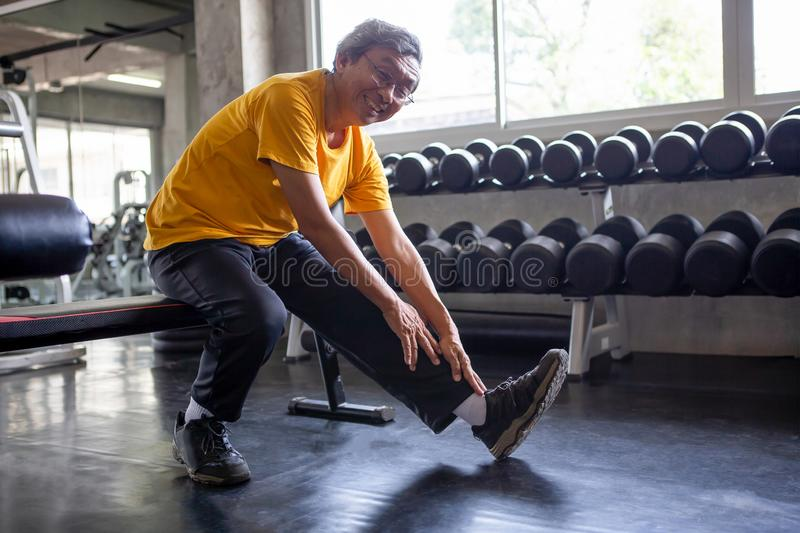 Senior asian sport man stretching his leg  in fitness gym . elder male exercising ,  working out , training , healthy ,Retirement stock photos