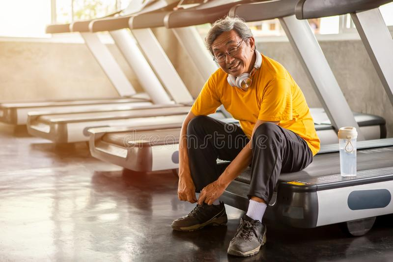 Senior asian sport man tying shoelaces on treadmill in fitness gym ready walking with headphone and water bottle . elder male royalty free stock photos