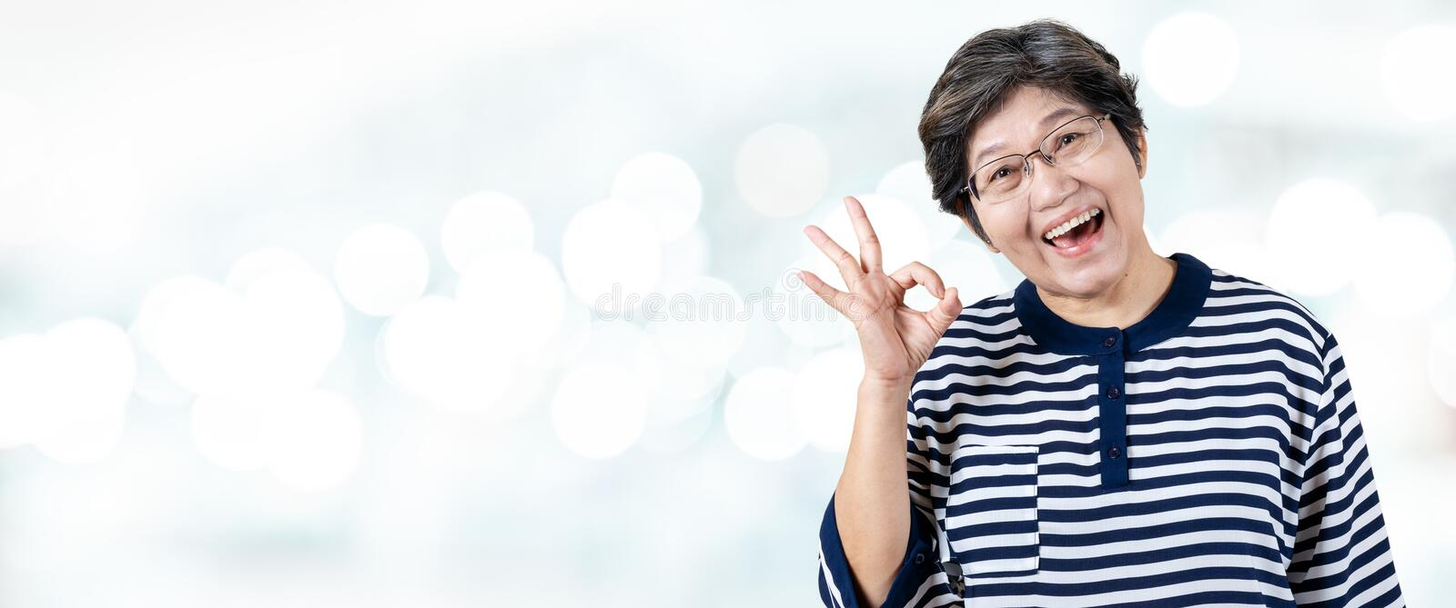 Senior Asian woman doing OK gesture royalty free stock photography