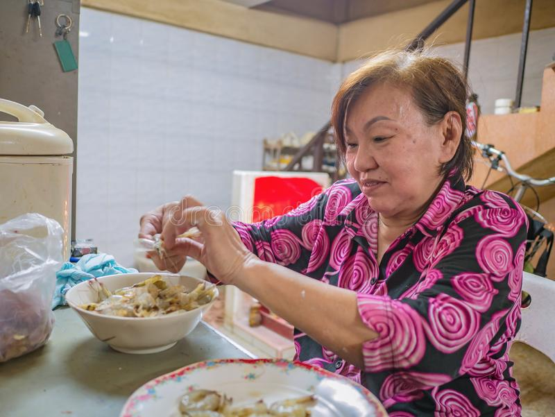 Senior asian women Focus on Peel shrimp by her hand. Senior asian woman Focus on Peel shrimp by her hand in her house royalty free stock photos