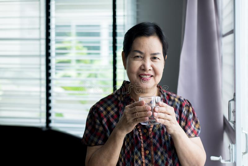Senior Asian woman hands holding a glass of water,,Happy and smiling,Elderly healthy and lifestyle concept royalty free stock photos