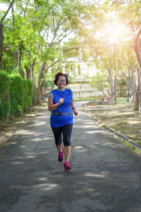 Senior asian woman happy jogging running in the park royalty free stock photography