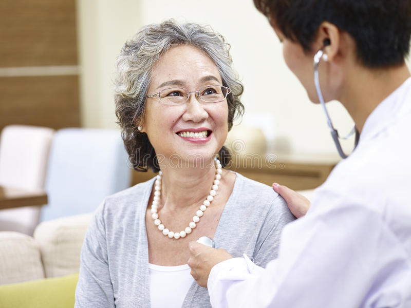 Senior asian woman having a physical check royalty free stock photos