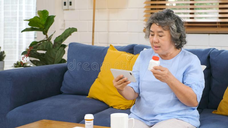 Senior asian woman holding bottle of pill make video conference phone call to doctor consulting about pill medical health care for royalty free stock photos