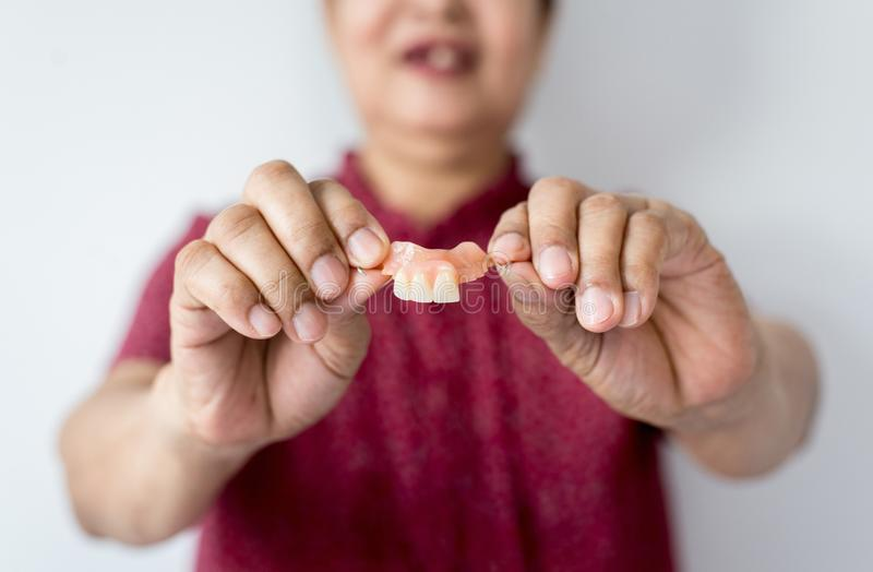 Senior asian woman is holding dentures in hands,Dental prosthesis,False teeth,Close up stock photos