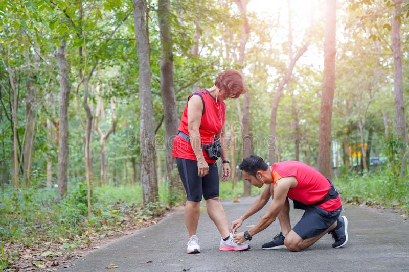 Senior asian woman with man or personal trainer tying shoe laces in the park stock images